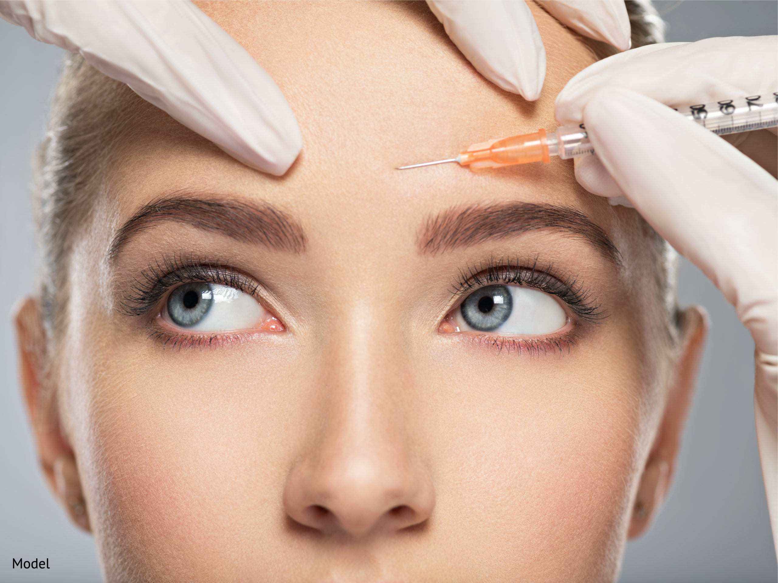 A woman receiving a face injection around the eyebrow area.