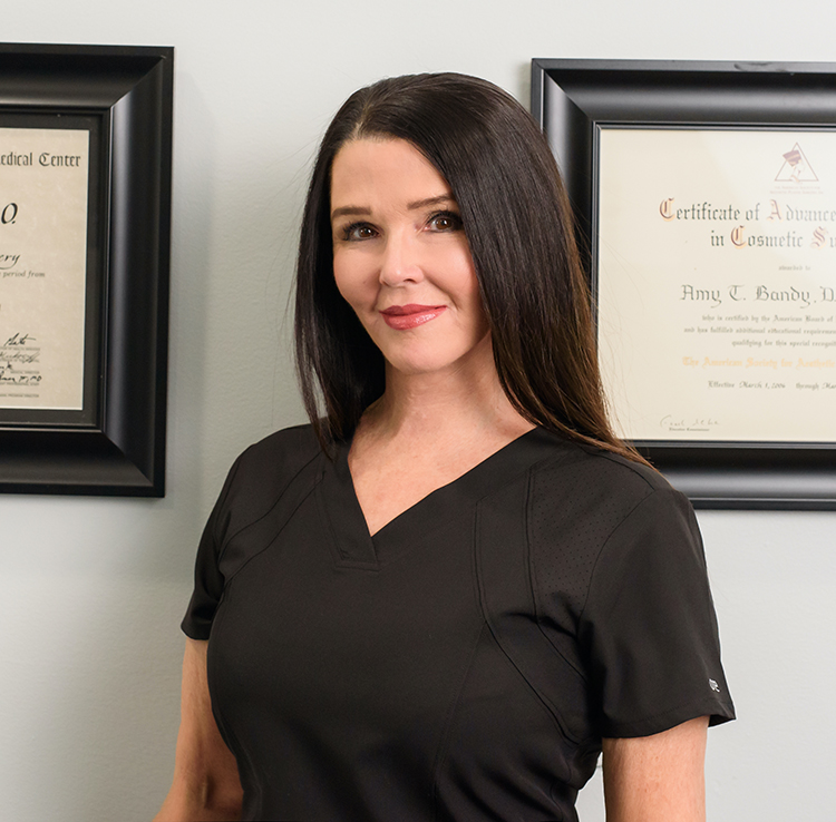 Image Doctor Amy Bandy in black scrubs standing in front of her medical degree